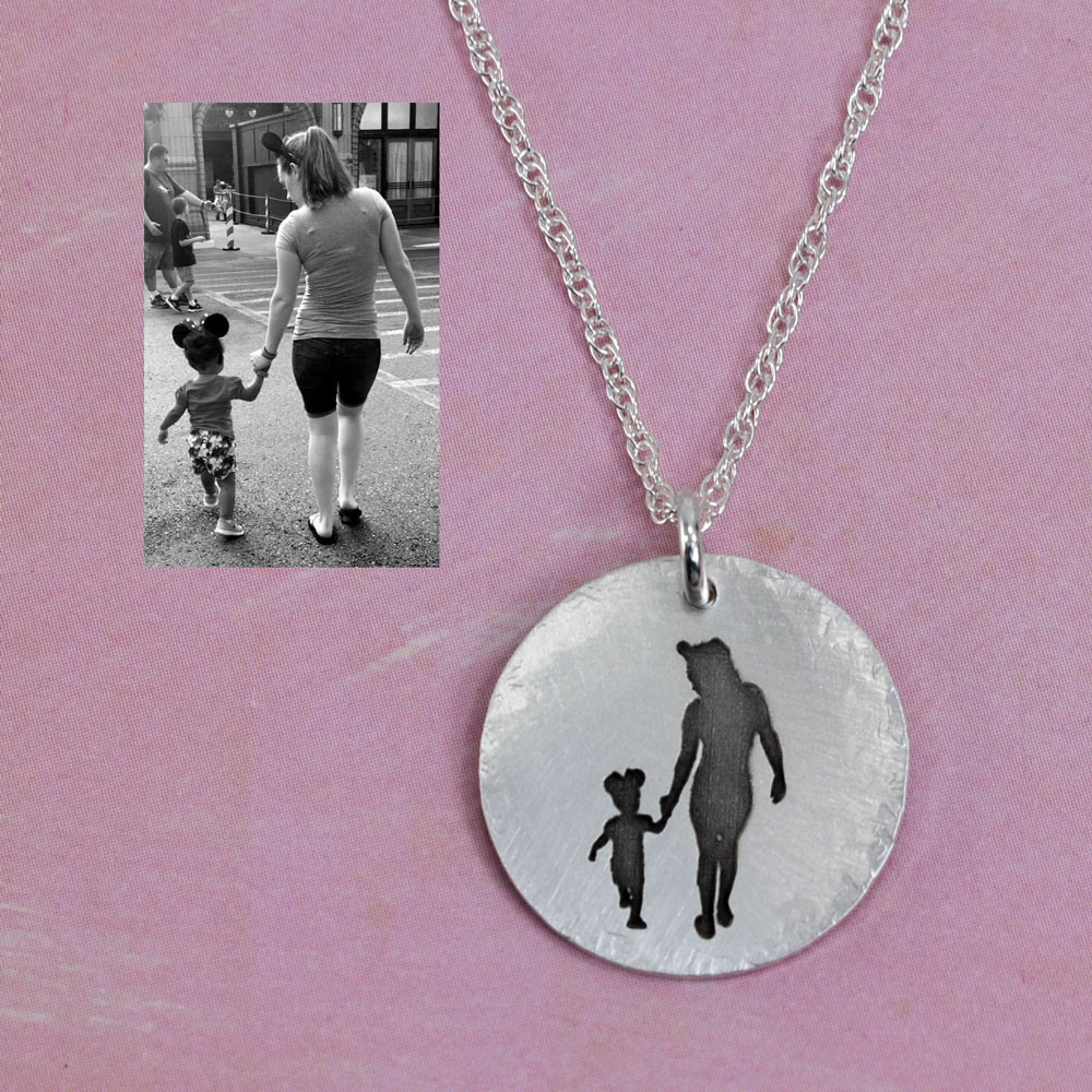 Sterling silver disc charm with etched silhouette of a photo of two people, with the original photo