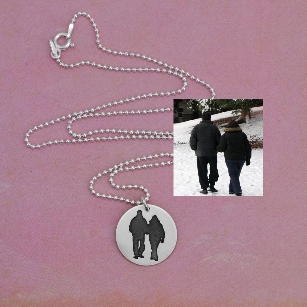 Sterling silver disc charm with etched silhouette of photo of two people, with the original photo