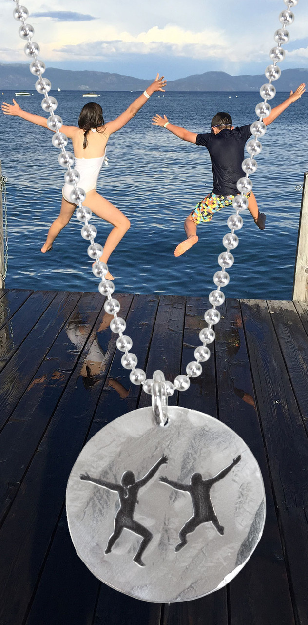 Sterling silver disc charm with etched silhouette of photo of two kids jumping off a dock, with the original photo