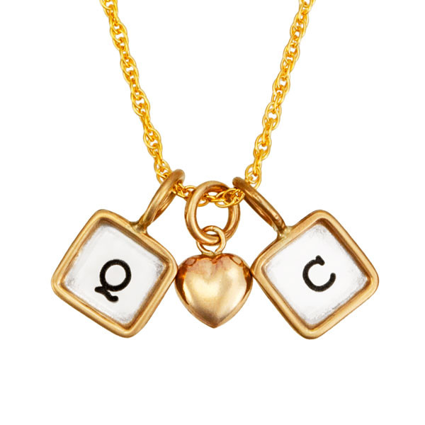 Mini squares with initials on gold chain, shown on white, close up