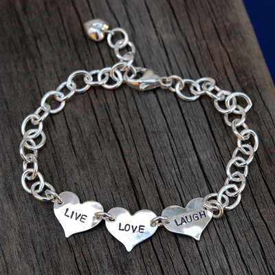 Small Hearts Hand Stamped Bracelet made of sterling silver, on a wood background