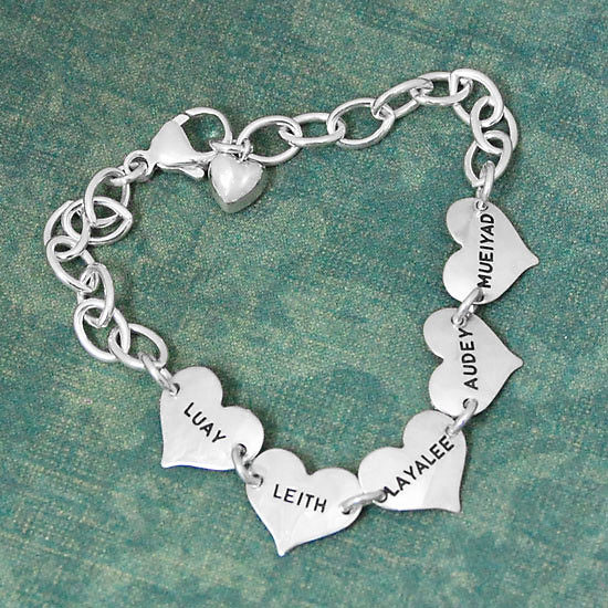 Small Hearts Hand Stamped Bracelet made of sterling silver, on a green background