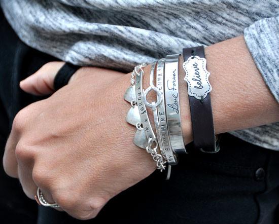 Stacked personalized bracelets, including stamped ID bracelet on a model