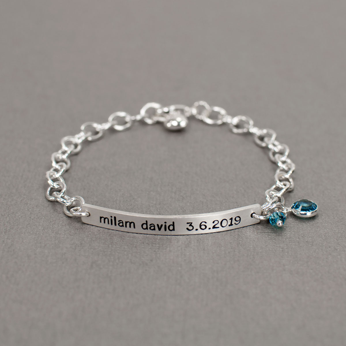Hand stamped ID Bracelet made from sterling silver, shown with birthstone on gray