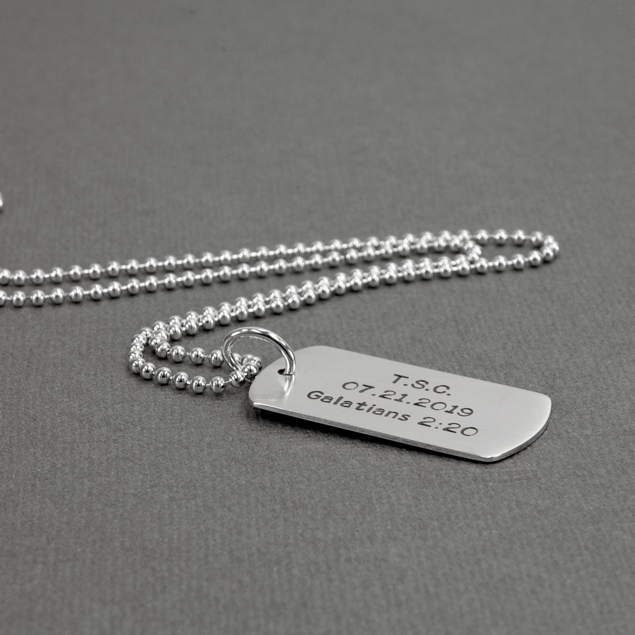 Custom hand stamped sterling silver military dog tag, personalized with names or phrases, shown from the side
