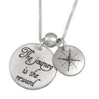 "Custom sterling silver necklace with ""The Journey is the Reward"" stamped in script, with another charm showing compass points, shown close up on white"