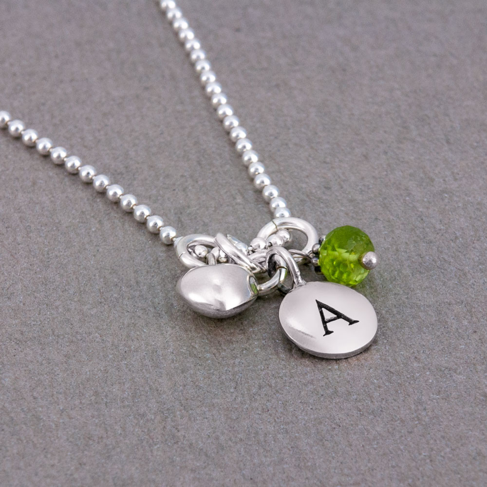 Silver Tiny Round Initial Charm necklace, shown close up from the side
