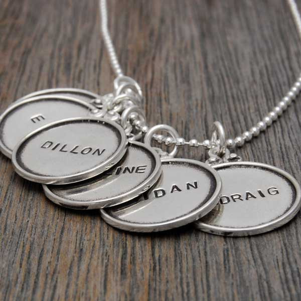 vintage style sterling silver circles with raised edges, hand stamped with names , shown close up from the side