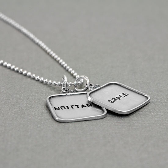 vintage style sterling silver hand stamped squares with raised edges, shown from the side on gray
