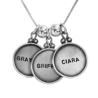 vintage style sterling silver circles with raised edges, hand stamped with names , shown close up on white