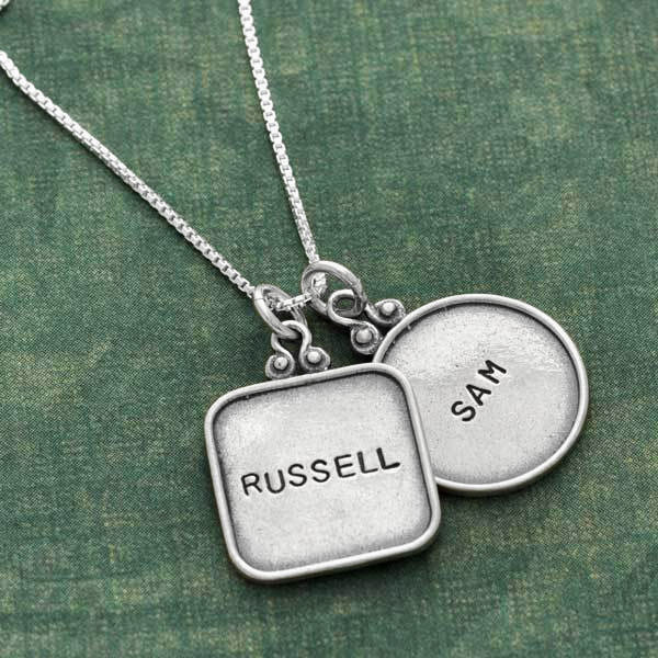 vintage style sterling silver hand stamped squares and circle with raised edges, shown close up on green background