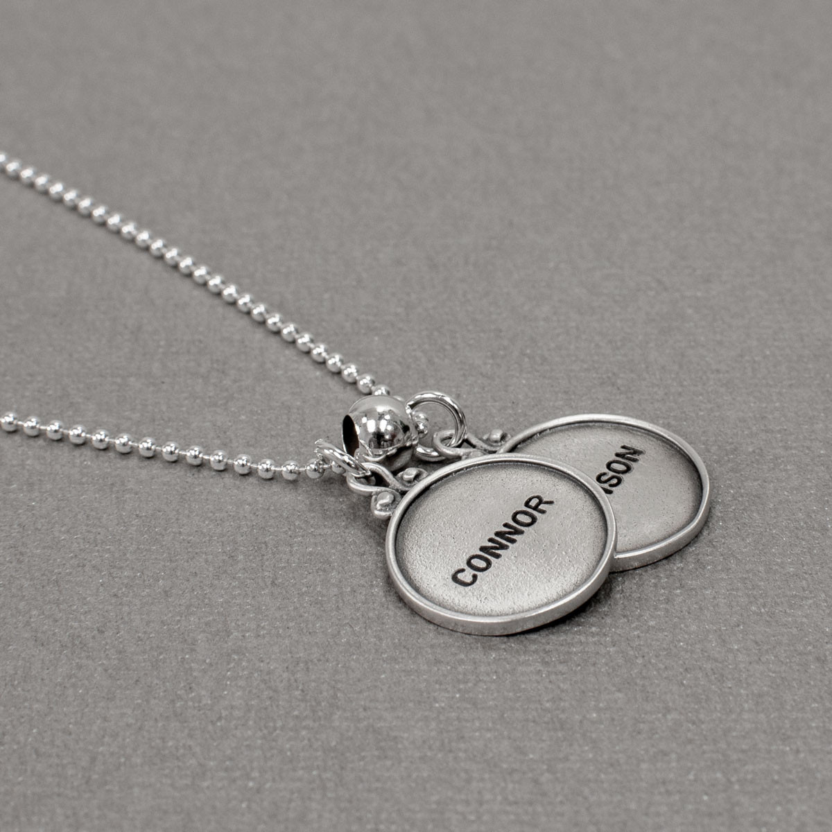 vintage style sterling silver circles with raised edges, hand stamped with names , shown from the side