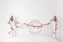 Christmas headboard scene, white vintage iron bed with simple red berries