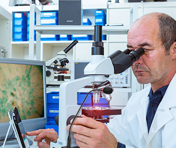 pathologist using microscope, tablet, and microphone