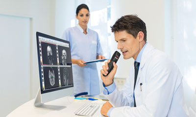 Doctor at desk with SpeechMike Premium Air using AirBridge