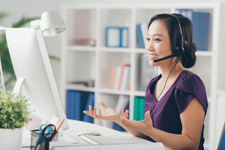 Woman sitting at a computer with headset on providing tech support for Dragon Medical One and Dragon Medical Practice Edition 4