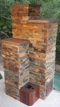 This is the completed build with stacked stone adhered. The cast fireclay caps, the clean-out door, and the metal top around the feed tube have been painted hi-temp brown metallic. The tallest stack of chimney flue liners (bell) is 7' (+ the cap), the one next to it is 6'. The chimney is connected to the back of the 6' bell.