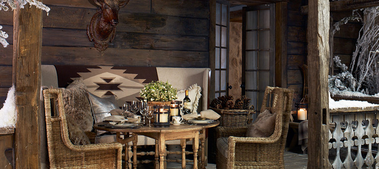 Cabin deck ready for entertaining with rustic dining table, wicker chairs and dinnerware.