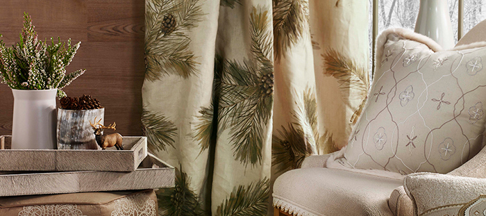 Beautiful drapes in rustic fabric featuring pine cones and pine needles. Elegant pillow is placed on nearby chair.