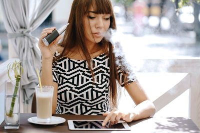Woman Vaping In A Caffee