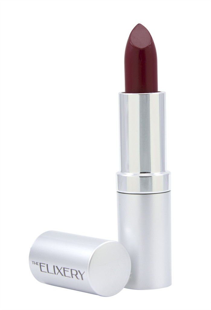 Deep red lipstick in a silver tube with cap sitting next to it.