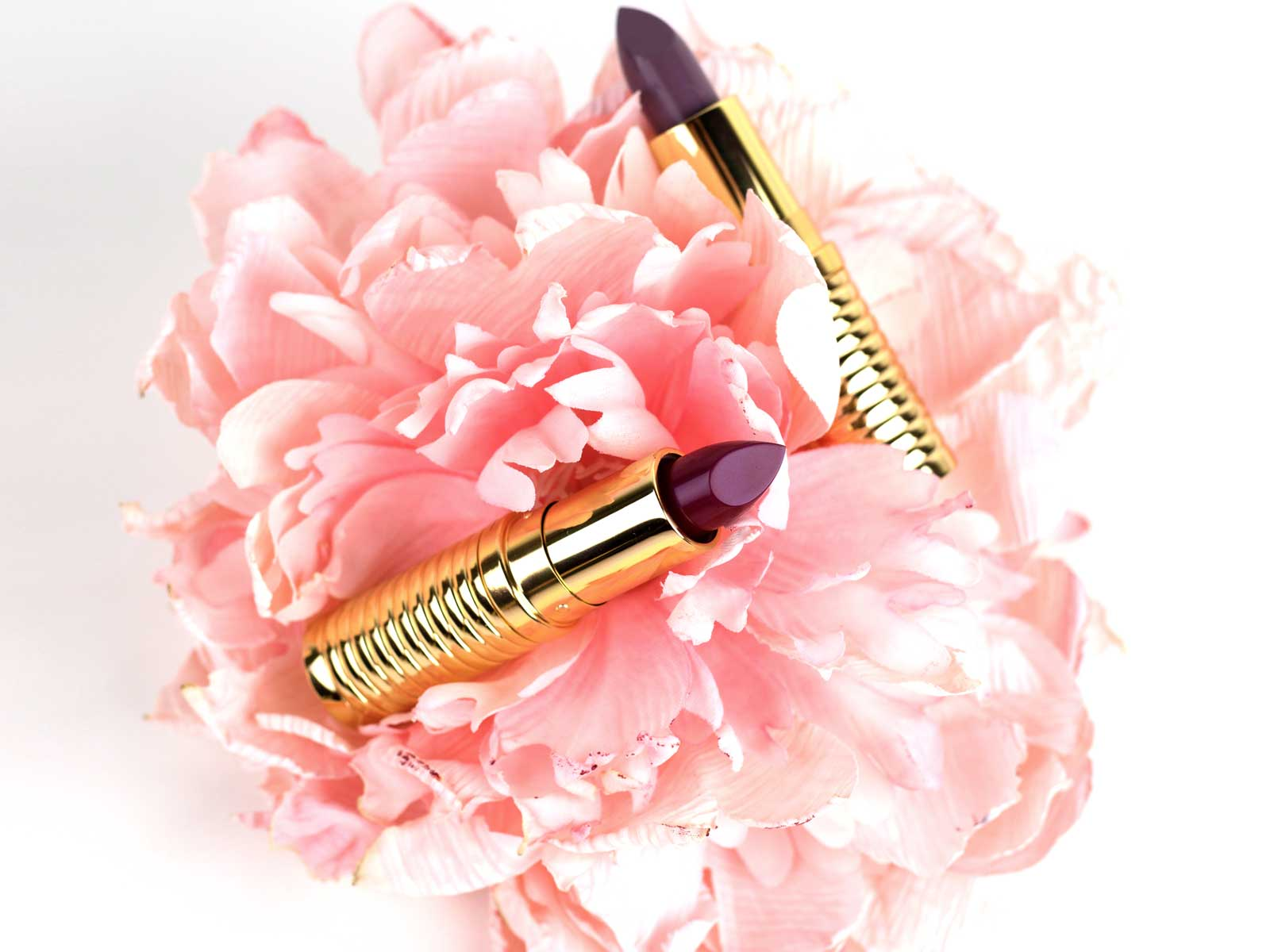 Lipstick in gold tube on Pink Peony Flower