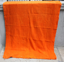 The top and bottom of the cloth is lighter due to the light conditions. The cloth is one solid uniform pumpkin orange color.