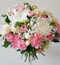 Rose and seasonal flowers including spray carnations, wax flower, baby's breath, disbuds and freesias