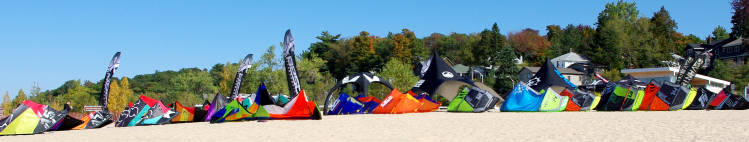 New kiteboarding gear lined up on the beach