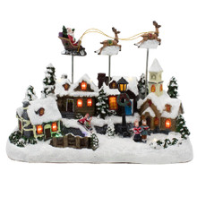 Watch Santa fly over a village with this Kurt Adler musical table piece. While the houses are LED-lit, Santa is seen moving and flying with his reindeers over this village. Two kids are seen sledding and two carolers singing. It plays eight different tunes.