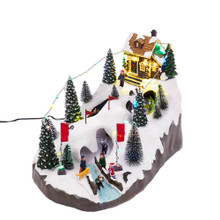 Bring the snowy slopes into your home this holiday with Motion LED Christmas Skiing Village from Kurt Adler. This piece features a house at the top of the slope with skiers ready to head down the slopes. Along the sides are various Christmas trees covered in snow. When activated, the string of lights along the trees and houses light up and the skiers start to move.