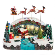 """Watch Santa deliver holiday cheer with this 10.5-in B/O LED Musical Village with Santa and Reindeer Table Piece from Kurt Adler! This table piece features Santa and three reindeer flying over a snow covered bridge. Children are crossing the creek under the bridge. One side, Mrs. Clause and a child in her lap are watching Santa fly overheard. The other side of the creek features a child ice skating. When activated, the tune """"Jingle Bells"""" plays and the lights go on."""
