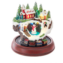 """Bring the snow into your home with this 7.5-in B/O LED Musical Village and Train Table Piece from Kurt Adler! This table piece features a snowman in the center with houses around. A child is sledding down the slopes beside the snowman. When activated, the tune """"Jingle Bells"""" plays, the lights go on, and the train below roars to life. This table piece is the perfect snowy addition into your holiday decoration without the chill."""