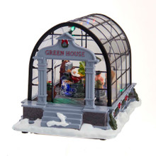 """What better way for Santa to warm up than to visit a greenhouse. This 5.5-in B/O LED Musical Greenhouse and Santa Table Piece from Kurt Adler features Santa hiding from the snow. He is taking a quick break from delivering gifts to all the good girls and boys. When activated, the lights go on and the tune """"Jingle Bells"""" plays."""