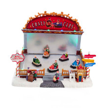 """Bring the fun of bumper cars home with this 9-in LED Light-Up Musical Bumper Cars Table Piece from Kurt Adler! This table piece features 5 kids in the rink while the families watch. When activated, the table piece lights up and the tune """"Jingle Bells"""" plays."""