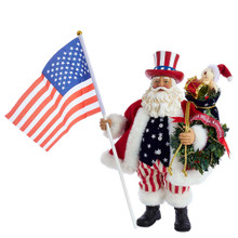 "Part of Kurt Adler's Fabriche collection, this 12.5-in Fabriche Patriotic Americana Musical Santa is a fun and festive addition to any holiday decoration! Perfect for Christmas or even the Fourth of July, Santa Claus is featured here wearing American flag-inspired detailing and holding a large American flag. For an extra festive touch, he has a bag of gifts and a green wreath. When wound up, this piece plays the tune of ""God Bless America."""