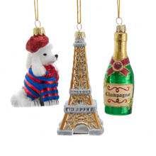 Decorate your home with this set of 4.5-in France Inspired Glass Ornaments from Kurt Adler. This set features a white poodle wearing a red beret and striped sweater, the Eiffel Tower, and a bottle of 2019 champagne. Show your pride with these country inspired ornaments!