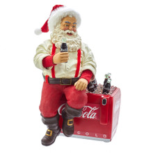 The Coca-Cola Santa Sitting on Cooler Table Piece from Kurt Adler is a great addition to your Christmas decoration. The table piece shows Santa sitting atop an open Coca-Cola cooler while dressed in a relaxed version of his Christmas suit, red and white plush hat, white button up shirt with sleeves rolled up, black belt and brown boots. In his hand he holds a glass bottle of coke. The cooler is filled with ice and glass bottles of their popular beverage.