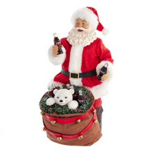 This 10.5-in Coca-Cola Santa with Polar Bear in Bag Table Piece from Kurt Adler is a great addition to your Christmas decoration. The table piece features Santa with bottles of Cokes in both hands. By his-feet is a sack wrapped in bells. A polar bear surrounded by bottles of Coca-Cola and garland pokes out from the sack. The perfect gift for any Coca-Cola fan!