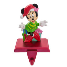 Hang up your favorite stocking this Christmas with this Minnie Mouse Stocking Holder from Kurt Adler! Perfect for the biggest Disney fans, Minnie Mouse is featured here wearing a green dress, red shoes, and a red and white Santa-style hat. She is standing in front of a pile of wrapped presents.