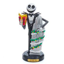 This 10-in Jack Skellington nutcracker from Kurt Adler is a fun and festive addition to any holiday decoration or nutcracker collection. Jack is wearing a black and white pinstripe tuxedo and he is holding a decorated present in one hand. His other hand is wrapped around a decorated tombstone.