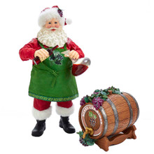 """This Kurt Adler 10.5-in Fabriche Wine Santa and Barrel is a fun and festive way to add to your holiday decoration, sure to appeal to wine lovers everywhere! Santa Claus is wearing a green apron with grapes while pouring wine into a decanter. This two piece set includes a wine barrel adorned with grapes with the words """"Merry Christmas"""" above the nozzle."""