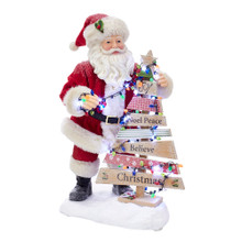 """This Kurt Adler 10.5-in Fabriche B/O Santa with Lighted Christmas Tree is a fun and festive way to add to your holiday decoration! Santa Claus is wearing the traditional red and white santa suit decorating a wooden Christmas word tree. The tree features the words: """"Joy,"""" """"Noel,"""" """"Peace,"""" """"Believe,"""" and """"Christmas""""."""