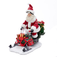 Add a fun, classic touch to your holiday decoration with this 12-in Fabriche Snowmobile Santa from Kurt Adler. Santa Claus is featured here in his traditional red and white suit and hat riding a snowmobile. The snowmobile is decorated and adorned with presents and garland.