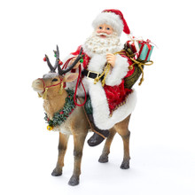Part of Kurt Adler's Fabriche collection, this 11.5-in Santa on Reindeer from Kurt Adler is a fun and festive addition to any holiday decoration. Santa Claus is featured here riding a reindeer wearing his traditional red and white suit while carrying a sack filled to the brim with presents. The reindeer is decorated with bells and decorated Christmas wreath.