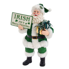 """Show off your Irish heritage with this 10.5-in Fabriche Musical Irish Santa Gift Box and Sign from Kurt Adler. This Santa is wearing a green Santa suit with a shamrock on the hat. In on hand are shamrock themed wrapped presents. His other hand holds up a sign that reads """"Irish you a Merry Christmas."""""""