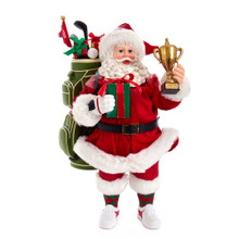 Celebrate the golfer in your life with this Kurt Adler 11-in Fabriche Golfer Santa with Golf Bag and Trophy! This table pieces features Santa wearing his classic Santa suit with crew socks and tennis shoes. Slung over his shoulder is his golf bag filled with golf clubs, presents, a golf ball and flag that reads the number 18. In his left hand, he holds a trophy. In his right hand, he holds a wrapped present. Santa's cheery smile is sure to brighten up your holiday decoration!