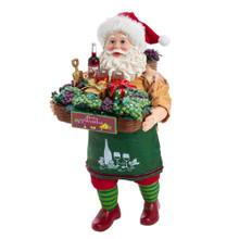 Bring the vineyard to your home with this 10.5-in Fabriche Santa Holding Big Wine Basket from Kurt Adler! This table piece features Santa after a long day of picking grapes. He is holding a basket overflowing with grapes, with wine, two wine glasses, a chalice, and wrapped presents. He is also carrying a pack basket, also overflowing with grapes. This unique Santa is sure to add a fun and unique touch to your holiday decoration!