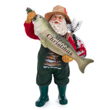"""This 10.5-in Fabriche Fishing Santa Holding Fish from Kurt Adler is perfect for the fisher in your life. Santa is featured wearing a fisher's hat and dark green fisher overalls. The overalls have images of various fish with the words """"Merry Christmas"""". The look is complete with Santa holding a fish with the words """"Merry Christmas"""" printed across and a sack of fishing gear slung over his shoulder. This table piece is the perfect addition to any fisher's holiday decoration!"""
