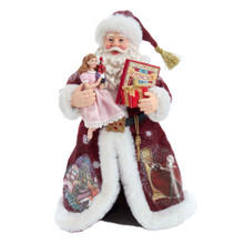 Add the magic of The Nutcracker to your home with this 11.5-in Fabriche Musical Nutcracker Suite Santa from Kurt Adler. Santa is featured here wearing a deep red robe with white fur trim. Santa's hat features a gold tassel and pictures of classic Nutcracker scenes are printed on his robe. In his left hand is a copy of The Nutcracker book and a wrapped present. In his right hand is Clara from The Nutcracker. The Clara doll is holding a nutcracker. This table piece is the perfect addition to any fan of The Nutcracker.